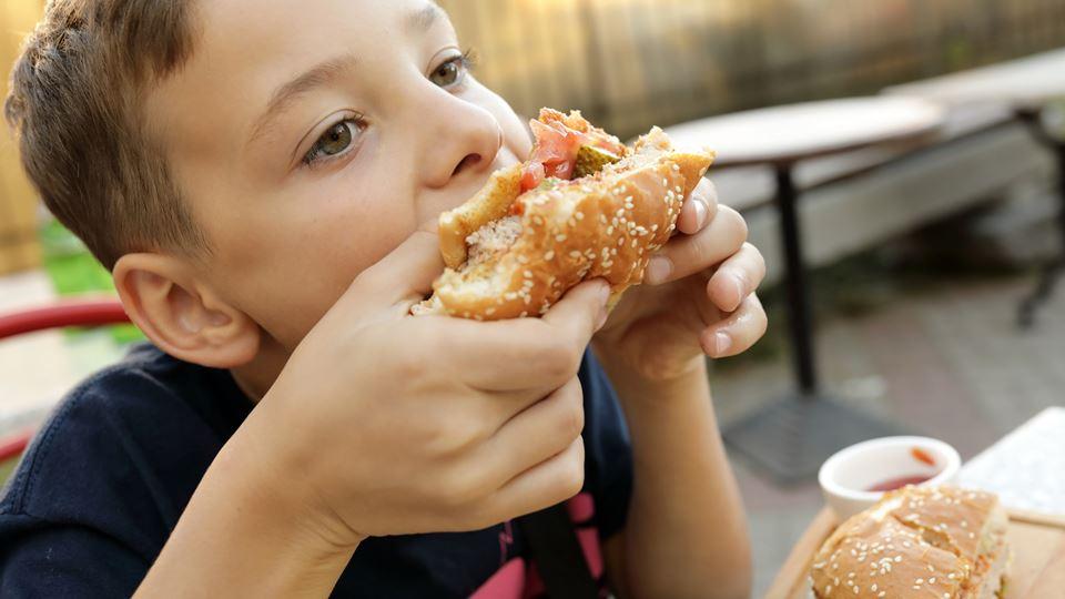 criança a comer hamburguer destaque