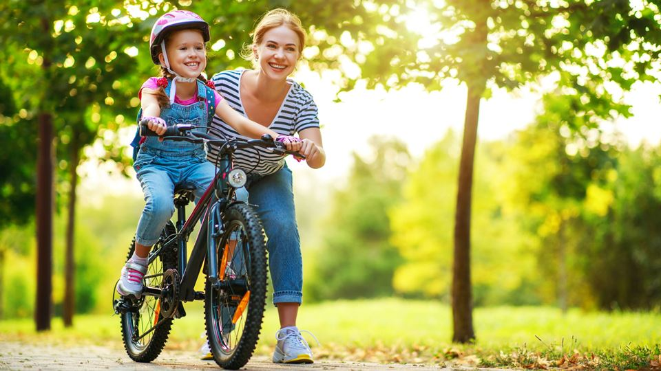 Mãe ensina filha a andar de bicicleta