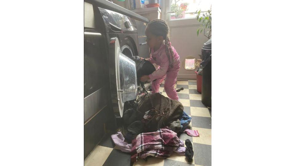 Menina a colocar roupa na máquina