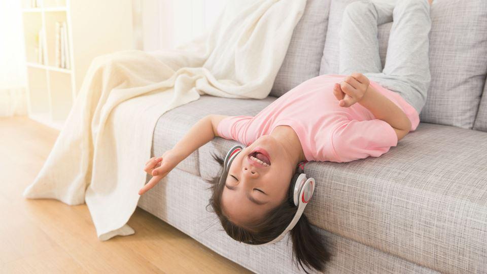 Menina a ouvir música no sofã